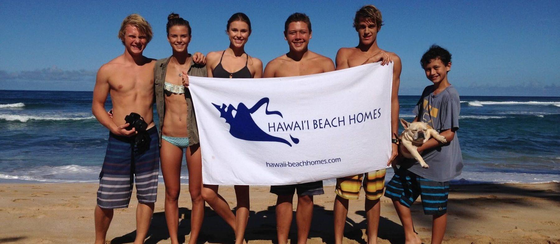 group on the beach holding the Hawaii Beach Homes flag