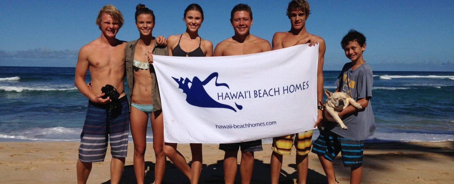 group on the beach holding the Hawaii Beach Homes flag