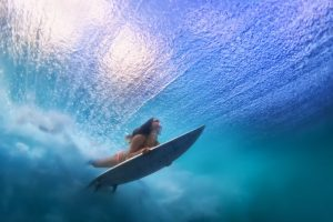 Lady underwater on her surfboard at one of the best Oahu Surf Spots